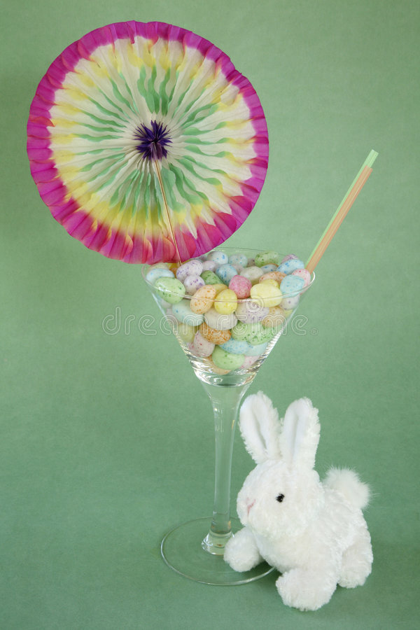 Jelly bean easter martini with bunny. Transparent martini glass filled with colorful speckled egg jelly beans from side with two colorful plain straws sticking royalty free stock photography