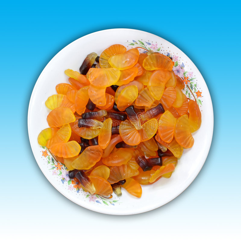 Jelly Candies. A plate of orange slice and cola bottle shaped jelly candies. Including clipping path stock images