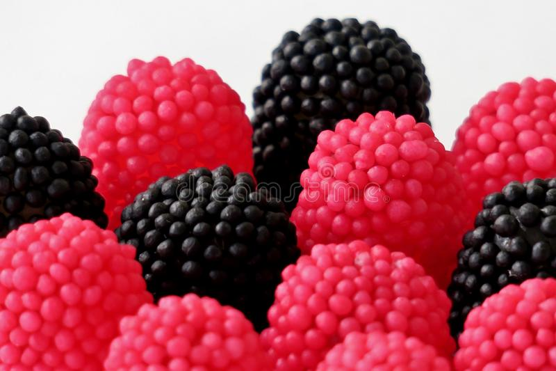 Jelly candies in the form of raspberries, red and black on a white background stock images