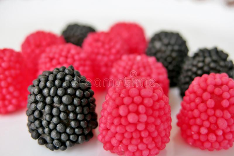 Jelly candies in the form of raspberries, red and black on a white background royalty free stock photos
