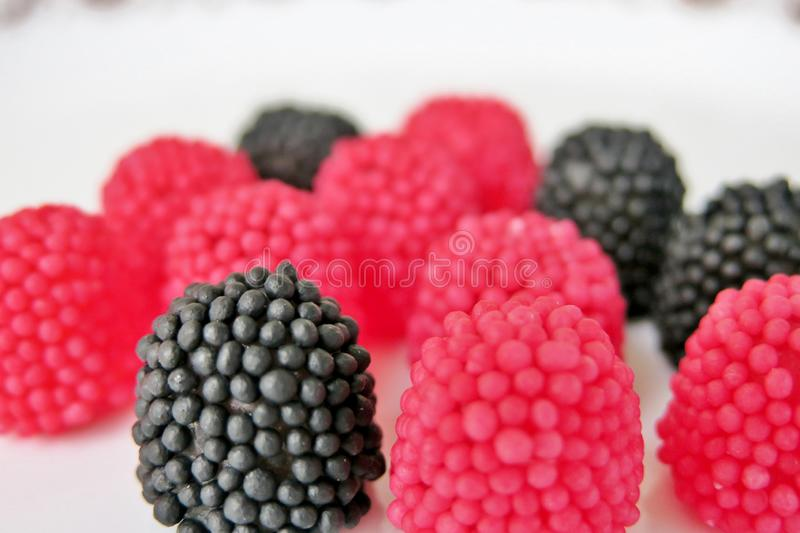 Jelly candies in the form of raspberries, red and black on a white background stock image