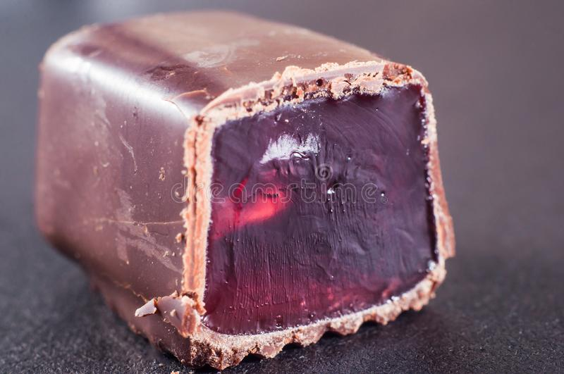 Jelly candy drenched in chopped chocolate. Red, pink dye in gelatin stock images