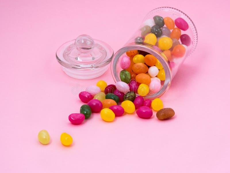 Jelly doces doces das cores diferentes dispersadas em um backgr cor-de-rosa foto de stock