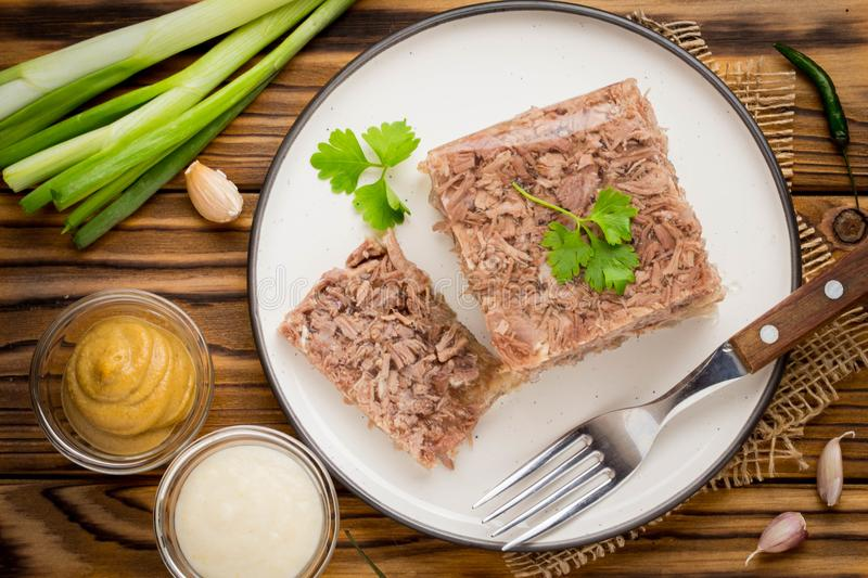 Jelly with meat, beef aspic, traditional Russian dish, portion. On a plate, mustard and horseradish royalty free stock image
