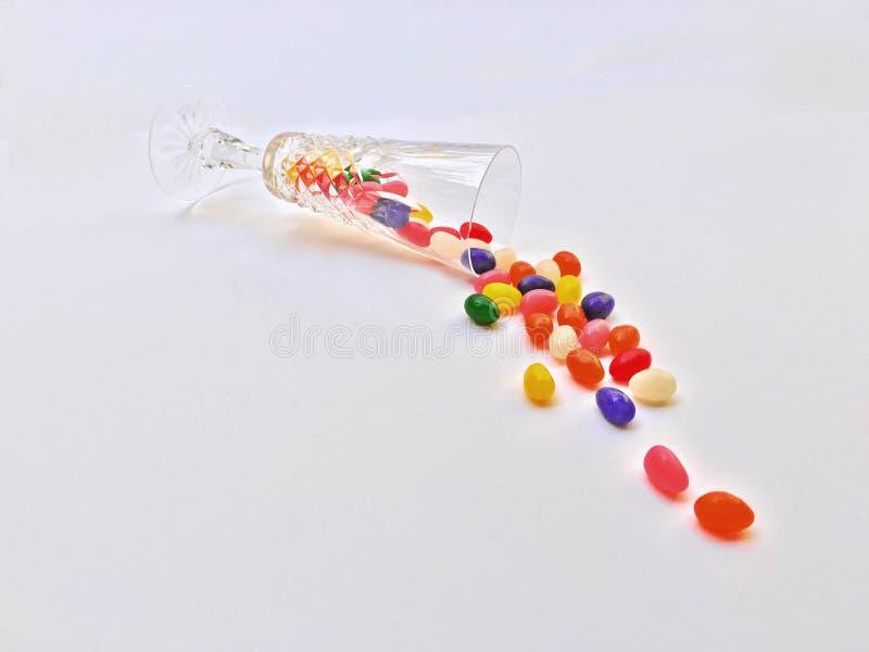 Jellybeans spiller ut ur ett champagneexponeringsglas på en vit backgroiund arkivbilder