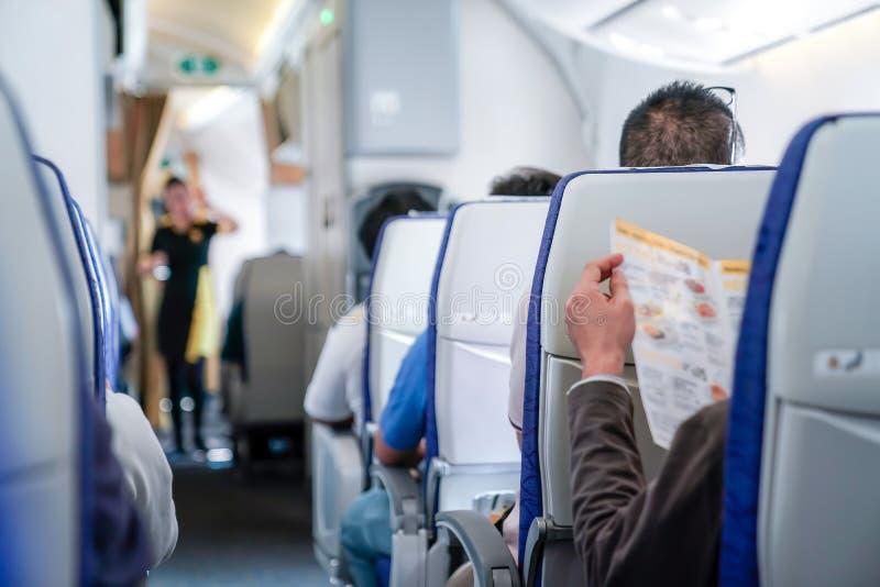 Jemand las das Menü im Flugzeug, bereiten Auftrag zur Stewardess lizenzfreie stockbilder