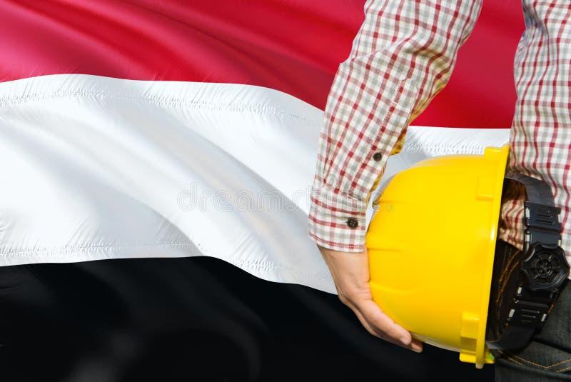 Jemeński inżynier trzyma żółtego zbawczego hełm z machać Jemen chorągwianego tło Budowy i budynku poj?cie fotografia royalty free