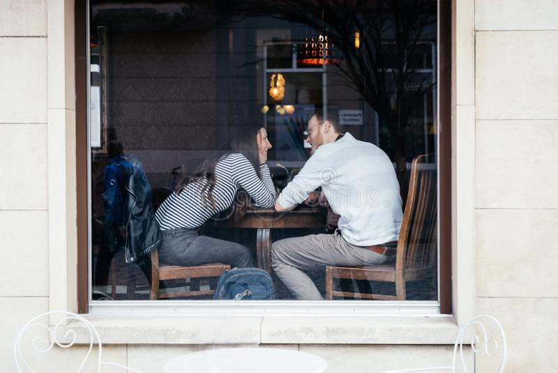 Jena, Alemanha 23 de mar?o de 2019 Pares bonitos no amor que senta-se no café perto da janela, vista da rua fotografia de stock