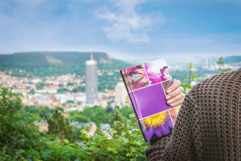 Jena, Duitsland 2 juni 2016 Het vrouwelijke notitieboekje van de studentenholding op de panoramische achtergrond van Jena royalty-vrije stock afbeeldingen