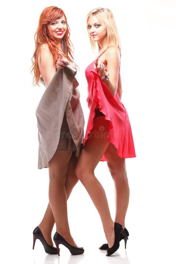 Jengibre bonito de dos mujeres con el blonde en vestidos fotos de archivo libres de regalías