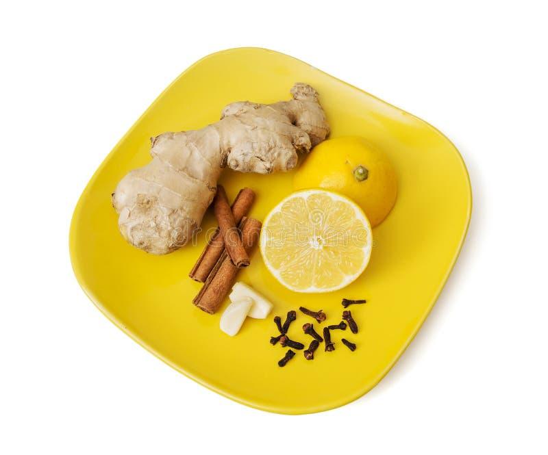 Jengibre, canela, limón, ajo y clavos en la placa fotos de archivo