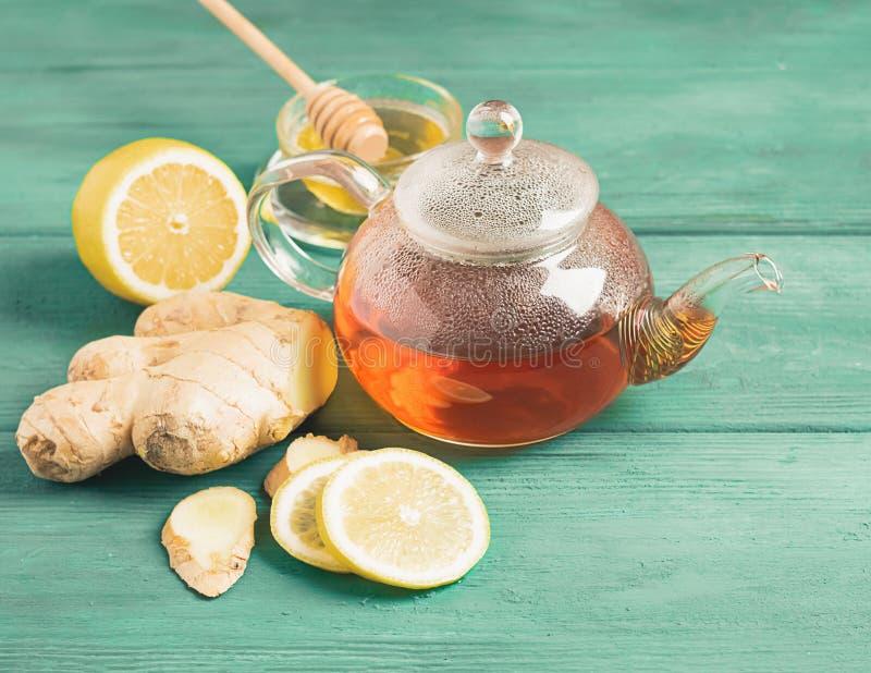 Jengibre del limón del té con la miel en una tetera transparente en un fondo rústico de madera Bebida sana para la salud del deto fotos de archivo