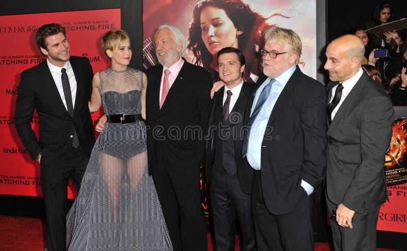 Jennifer Lawrence y Liam Hemsworth y Donald Sutherland y Josh Hutcherson y Philip Seymour Hoffman y Stanley Tucci fotos de archivo