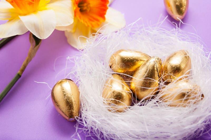 Jerarquice con los huevos y los narcisos en un fondo azul pascua fotos de archivo libres de regalías