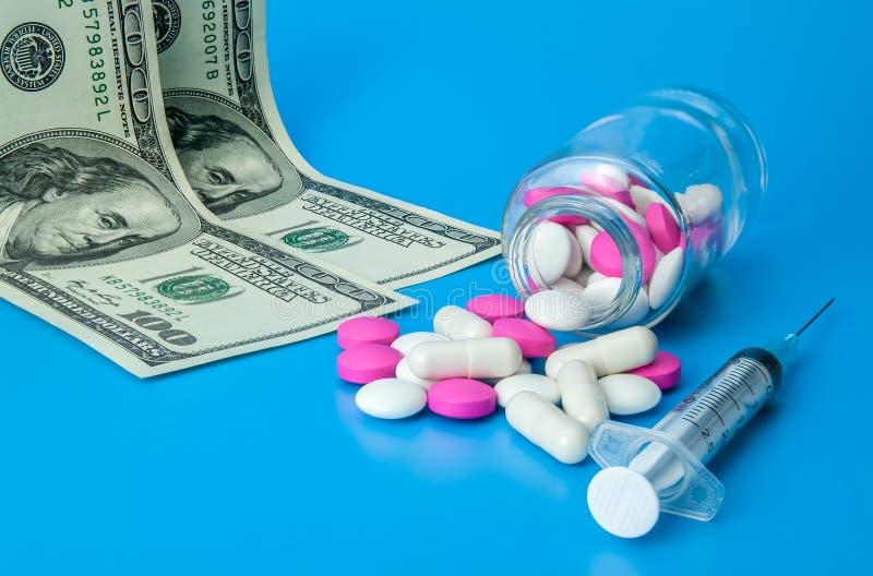 Jeringuilla, dólares y píldoras rosadas y blancas en un fondo azul brillante imagen de archivo