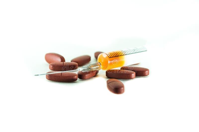 Jeringuilla para la inyección con la vacuna y las tabletas de la medicina en un fondo blanco foto de archivo libre de regalías