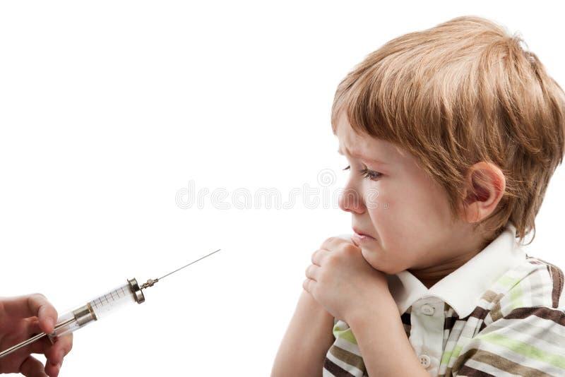 Jeringuilla que inyecta al niño foto de archivo