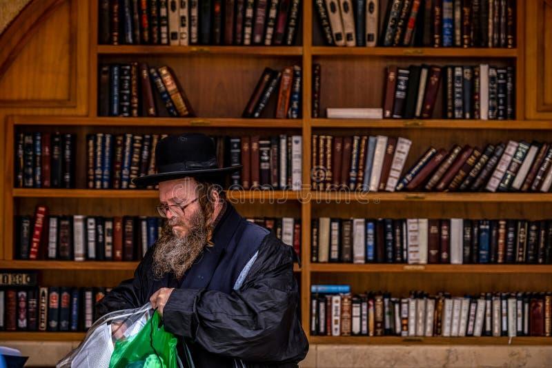 23/11/2016 Jerozolima, Izrael, żyd siedzi blisko półek z religijnymi książkami na kwadracie zdjęcie royalty free