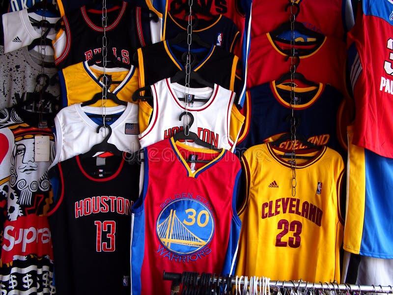 Jerséis clasificados de los deportes en venta en una tienda de ropa imagen de archivo