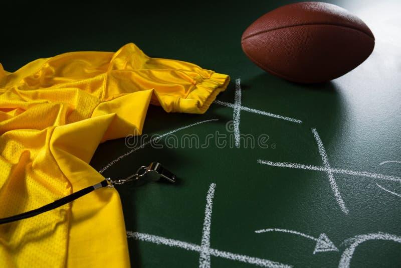 Jersey, свисток и футбол американского футбола лежа на зеленой доске с стратегией нарисованной на ей стоковое фото