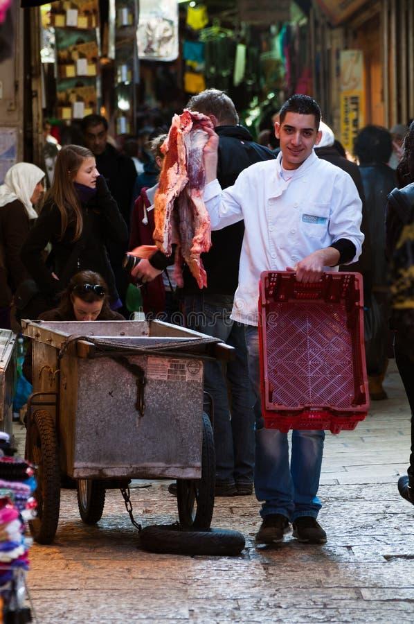 Jerusalém, em dezembro de 2012: O carniceiro novo troca a carne no souk do Jerusalém foto de stock royalty free