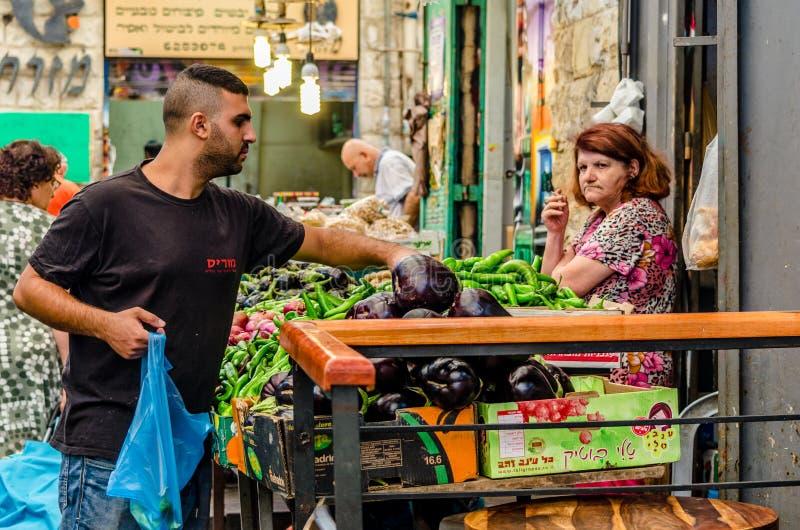 Jerusal?m, Israel 16 de agosto de 2016: Mulher que vende vegetais do homem no mercado no Jerusal?m, Israel imagens de stock