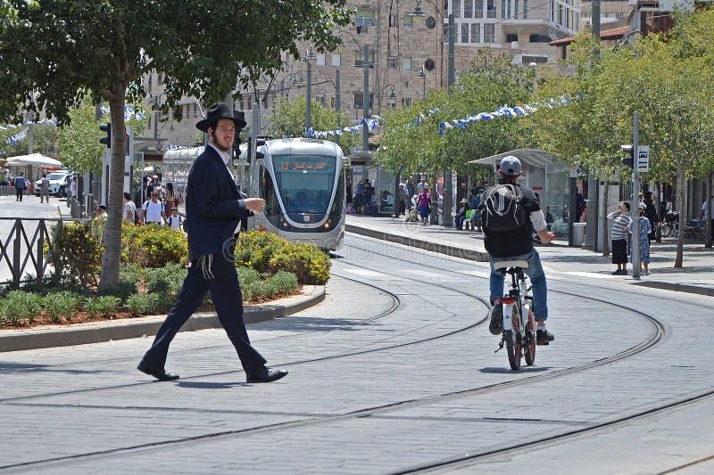 Jerusalém, Israel - 18 de maio de 2018: Um judeu religioso cruza a estrada em uma trilha do bonde Violação de regras de tráfego,  imagem de stock