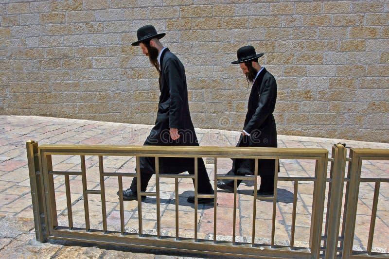 Jerusalén, Israel, 06 07 2007 dos judíos con las barbas en los sombreros negros y los trajes negros están caminando abajo de la c fotos de archivo