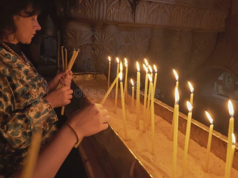 JERUSALÉN, ISRAEL SEPTIEMBRE, 20, 2016: dos mujeres encienden velas en la iglesia del sepulcro santo imagenes de archivo