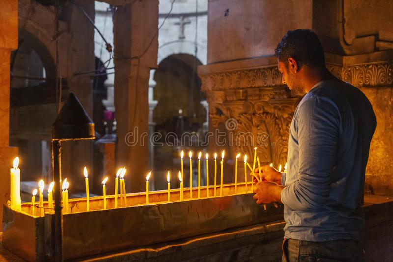 Jerusalén, Israel, 09/11/2016: Un hombre de creencia pone velas y ruega en el templo de Santo Sepulcro foto de archivo libre de regalías
