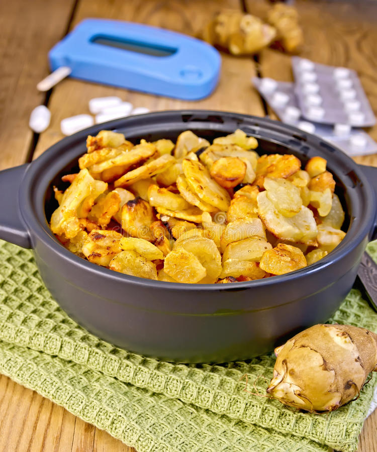 Jerusalem artichokes roasted in pan with meter stock photography