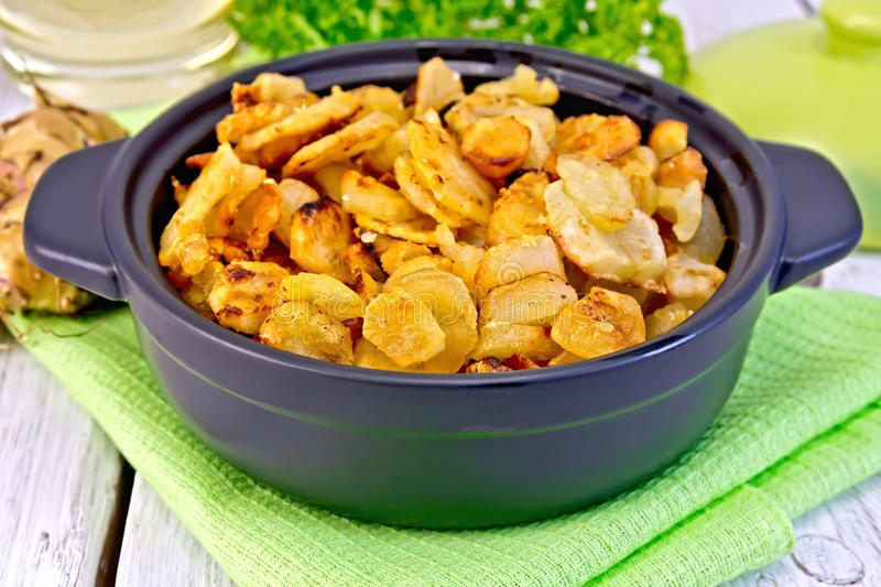 Jerusalem artichokes roasted in pan on napkin. Jerusalem artichokes roasted in a roasting pan, fresh tubers on a napkin, parsley, vegetable oil on a background royalty free stock images