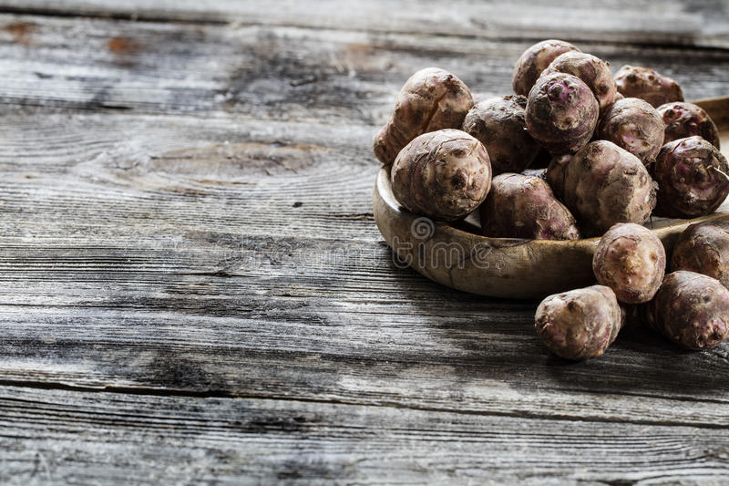 Jerusalem artichokes or topinambour roots on old wood. Vegetable still life - Jerusalem artichokes or topinambour roots on old wooden background for genuine home royalty free stock photography