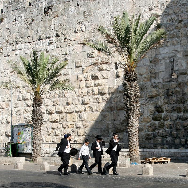 Jerusalem, Israel, 06.07.2007 four Jewish young men walk down the street along the stone wall. Outdoors, outside royalty free stock image