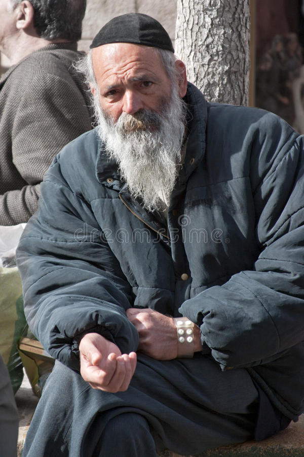 JERUSALEM, ISRAEL - MARCH 15, 2006: Purim carnival. Portrait of a tramp begging. An elderly man in a black jacket, kippa and beard. Purim is celebrated stock images