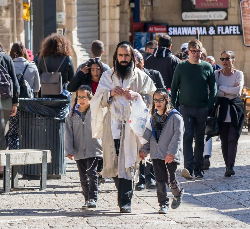 A religious and his sons walk the street near the Jaffa Gate in the old city of Jerusalem, Israel. Jerusalem, Israel, March 09, 2019 : A religious and his sons stock photo