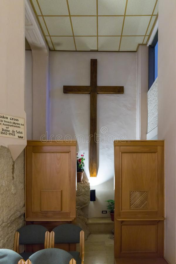 A large wooden cross brought by French pilgrims hangs on the wall on the wall in the lower hall in Church of Saint Peter in Gallic stock photography