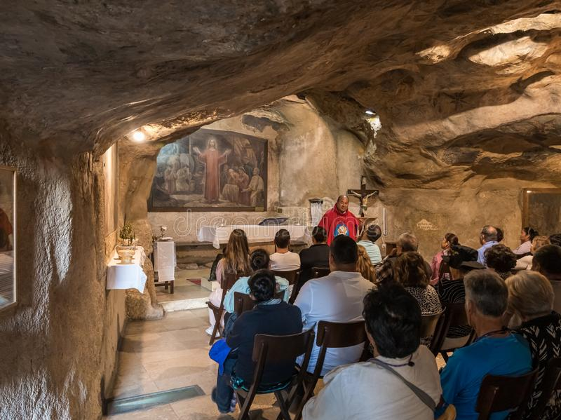 A preacher gives a sermon to visitors in the hall of the Grotto of Gethsemane on foot of the mountain Mount Eleon - Mount of royalty free stock image
