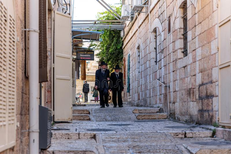 Two religious Jews walk and talk down the street near Jaffa Gate in the old city of Jerusalem, Israel royalty free stock image