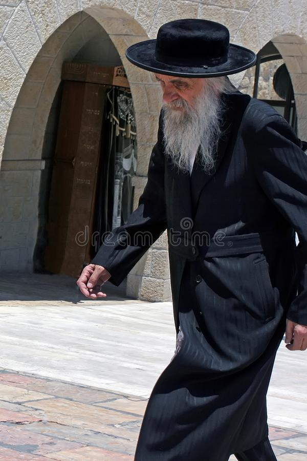 Jerusalem, Israel, 06.07.2007 an old gray-haired with a beard in a black hat and a black robe walking down the street royalty free stock image