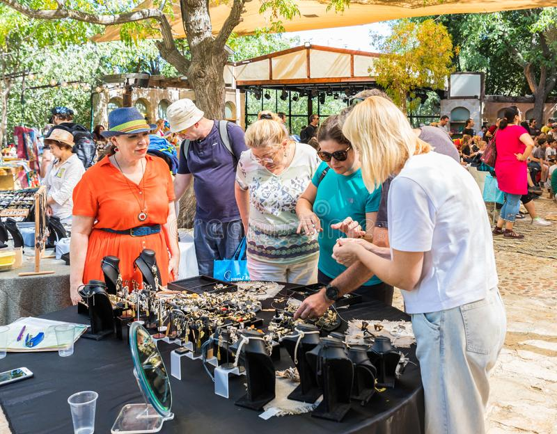 Visitors view handmade jewelry on the counter at the annual festival Jerusalem Knights. Jerusalem, Israel, September 30, 2019 : Visitors view handmade jewelry on royalty free stock photo