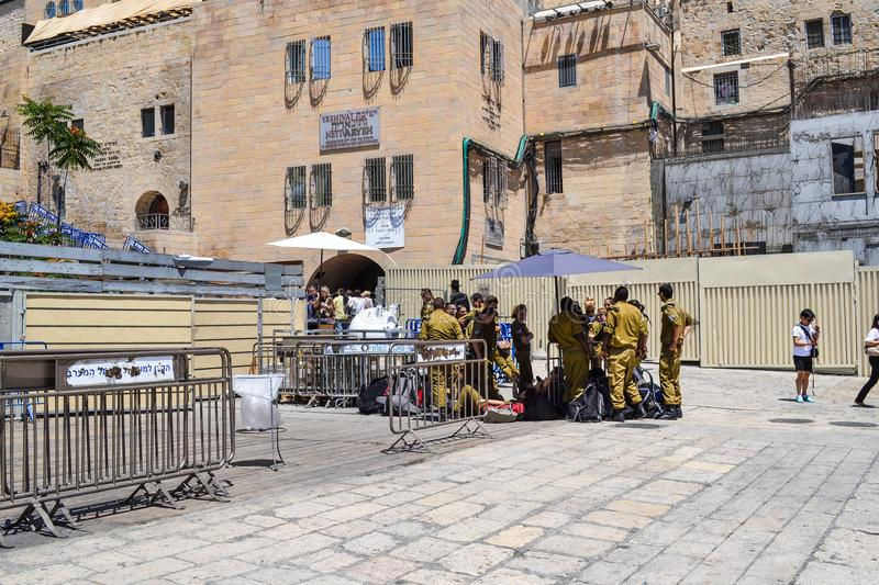 JERUSALEM - May 20, 2014. Israeli soldiers rest in the shade on the square near the Western Wall in Jerusalem royalty free stock images
