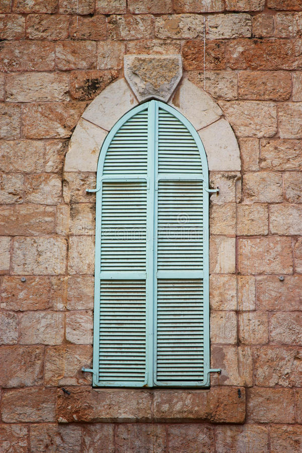 Jerusalem's ancient building's wall with blue aqua window shutters. retro filtered image.  stock photography