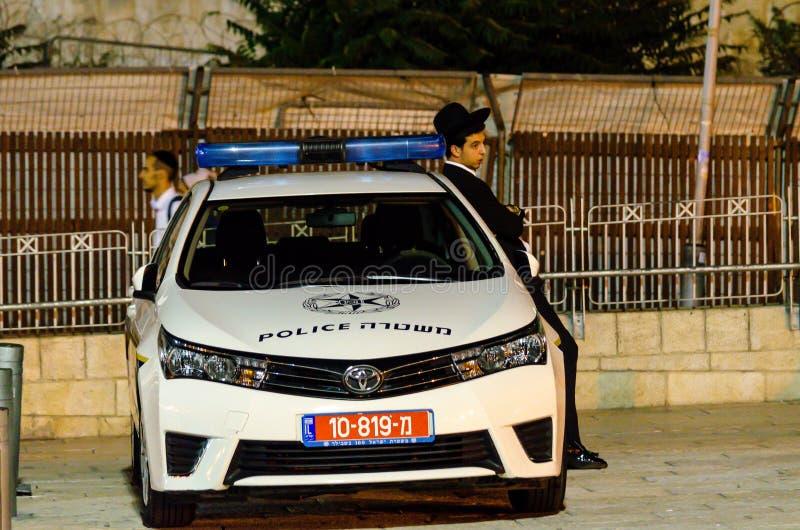 Jeruzalem/Israël 17 Augustus, 2016: Jonge Joodse Orthodoxe mens die op politiewagen in Jeruzalem, Israël leunen stock afbeelding