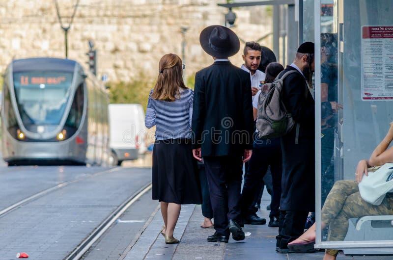 Jeruzalem, Israël 17 Augustus, 2016: Joodse Orthodoxe man en vrouw die op de trein in Jeruzalem, Israël wachten stock afbeeldingen