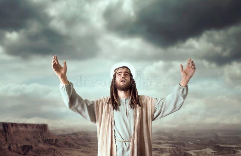 Jesús que ruega con sus manos para arriba contra el cielo nublado foto de archivo