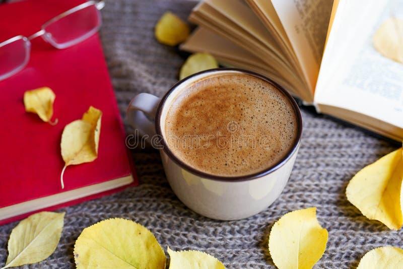 Jesień flatlay z filiżanka kawy, książki, szkła, kolor żółty opuszcza i rezerwuje na szalika tle zdjęcia royalty free
