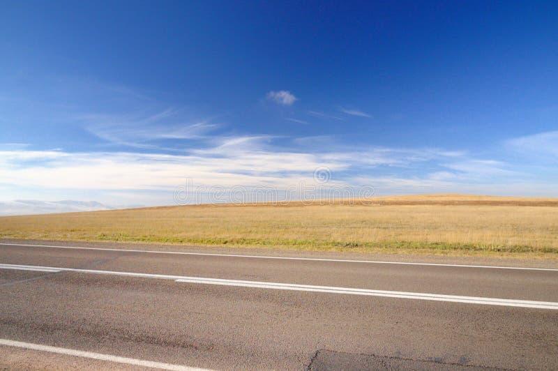 Jesień krajobraz z asfaltową drogą wzdłuż czyścić rolniczego pola pod zmrokiem - niebieskie niebo z spektakularne chmury fotografia stock