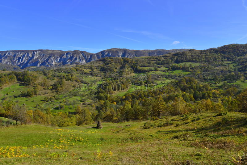 Jesień krajobraz z górską wioską, haystack i górami przy odległością w Rumunia, obrazy stock