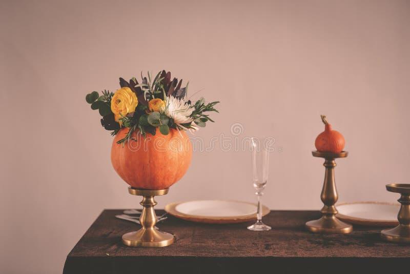 Jesień kwiecisty bukiet w dyniowej wazie dla Halloween diety naczynia szklana miara setu sto?u ta?my wody zdjęcie stock